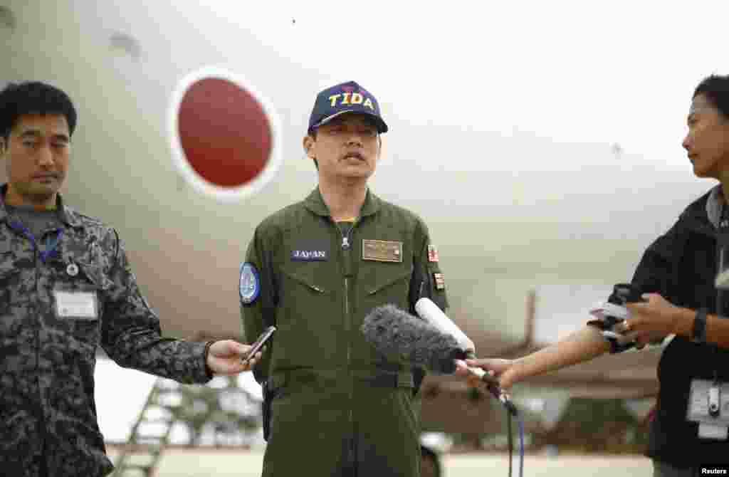 Japan's Maritime Self-Defense Force Commander Hidetsugu Iwamasa speaks to the press in front of one of their P-3C Orion aircraft currently at RAAF Base Pearce near Perth, Australia, April 4, 2014.