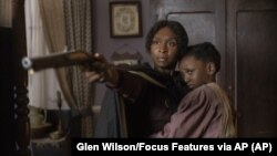 "This image released by Focus Features shows Cynthia Erivo as Harriet Tubman, left, and Aria Brooks as Anger in a scene from ""Harriet."""