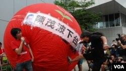 香港立法會議員梁國雄(右)腳踢巨型氣球,喻意「踢走陳茂波」 (美國之音湯惠芸拍攝)