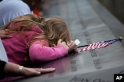 Family members visit the south reflecting pool during 10th anniversary ceremonies at the Sept. 11 memorial, Sunday Sept. 11, 2011, in New York. (AP Photo/Todd Heisler, Pool)
