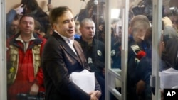 Former Georgian President Mikheil Saakashvili stands behind the glass and talks to reporters before the hearing in a court room in Kyiv, Ukraine, Dec. 11, 2017.