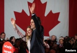 Liberal Party leader Justin Trudeau waves while accompanied by his wife, Sophie Gregoire, as he gives his victory speech after Canada's federal election in Montreal, Quebec, Oct. 19, 2015.