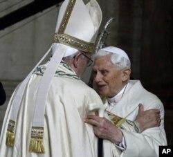 Paus Emeritus Benediktus XVI, kanan, memeluk Paus Francis di Basilika Santo Petrus selama upacara yang menandai dimulainya Tahun Suci, di Vatikan, Selasa, 8 Desember 2015. (Foto: AP)