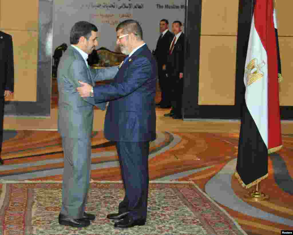 Egyptian President Mohamed Morsi greets Iran's President Mahmoud Ahmadinejad before the opening OIC summit in Cairo, February 6, 2013.