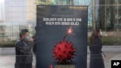 Para pejalan kaki mengenakan masker melewati poster kesadaran menjaga jarak sosial di tengah pandemi COVID-19, di Seoul, Korea Selatan, 7 Desember 2020. (Foto: dok).