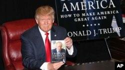 Donald Trump, candidat aux primaires républicaines pour la présidentielle américaine de 2016, présente son livre de campagne, 3 novembre 2015. (Photo by Greg Allen/Invision/AP)