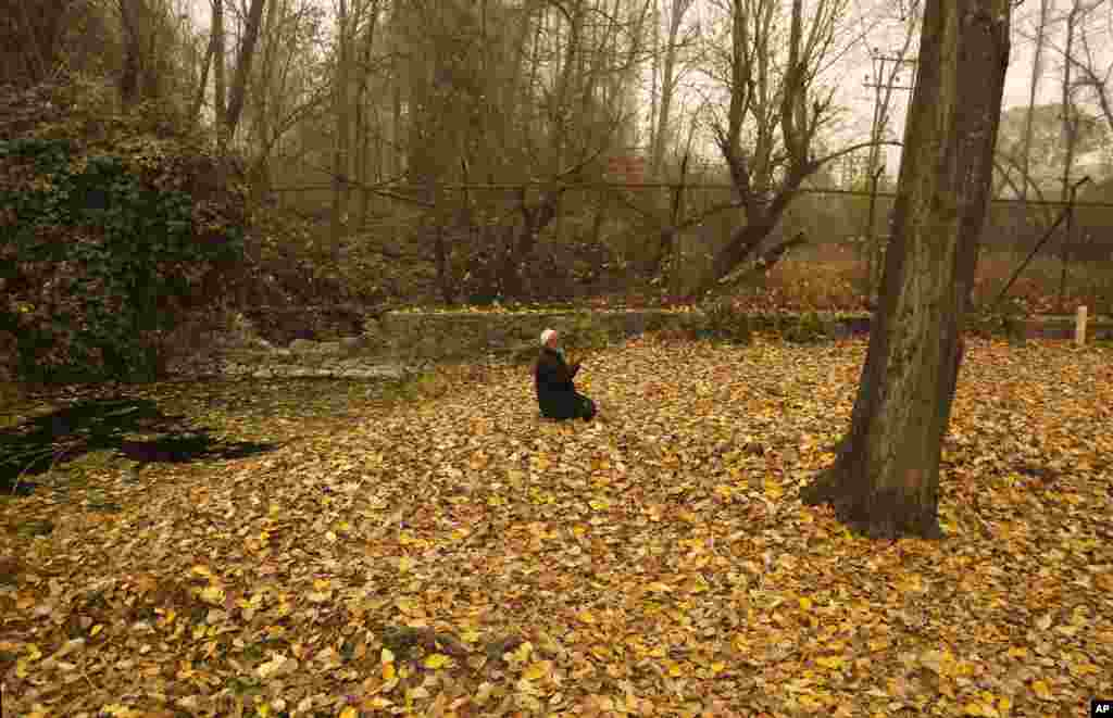 An elderly Kashmiri Muslim man prays on dried leaves on a cold and foggy day in Srinagar, Indian-controlled Kashmir.