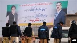 Hình treo trên tường là cựu Thủ tướng Pakistan Yousuf Raza Gilani (phải) và con trai Abdul Qadir Gilani
