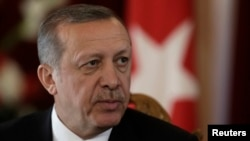 FILE - Turkish President Recep Tayyip Erdogan listens during a news conference in Riga.