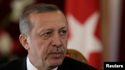 FILE - Turkish President Recep Tayyip Erdogan listens during a news conference in Riga, Oct. 23, 2014.
