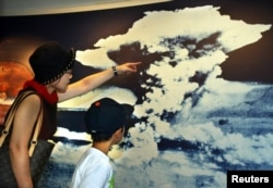 FILE - A mother and son look at a picture of the mushroom cloud atomic bomb blast as they visit Hiroshima Peace Memorial Museum in Hiroshima, Aug. 5, 2002. The bomb dropped on Hiroshima virtually leveled the entire city.
