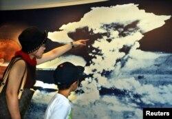 Seorang ibu dan putranya melihat gambar awan jamur bom atom di Museum Memorial Perdamaian di Hiroshima.