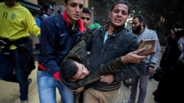 A protester wounded in clashes with security forces is evacuated from the site in the Mohandiseen district of Cairo, Egypt, Saturday, Jan. 25, 2014.