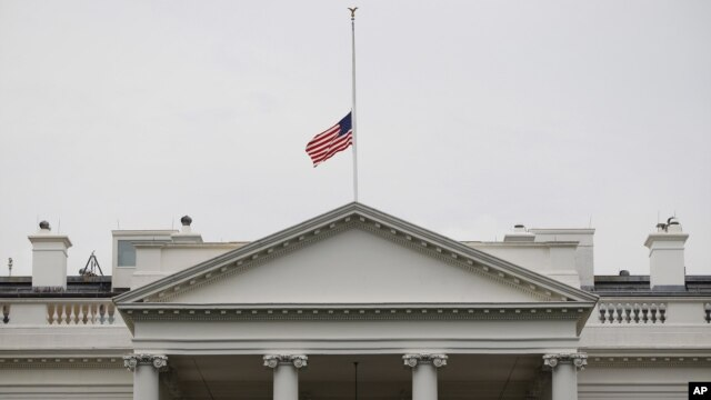 A U.S. flag is seen at half-staff over the White House in Washington, Friday, July 20, 2012. President Barack Obama ordered the flag to be lowered in the aftermath of the tragic mass shooting at a movie theater in Aurora, Colorado.