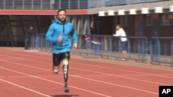 In this image taken on June 27, 2013, from TV provided by ab productions via APTN, Oscar Pistorius runs at the University of Pretoria, South Africa, during his first training session since the killing of girlfriend Reeva Steenkamp.