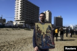 FILE - A man holds an icon against the backdrop of crumbling buildings destroyed in Cyprus's 1974 war during a celebration for Orthodox Epiphany for the first time in decades at Famagusta, Cyprus, Jan. 6, 2016.