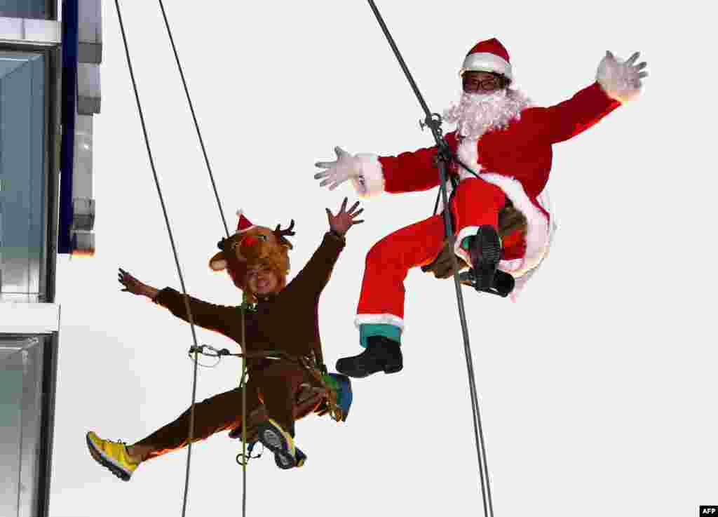 Workers in Santa Claus (R) and reindeer (L) costumes are pictured as they clean windows outside a shopping mall along Tokyo's waterfront, Japan.