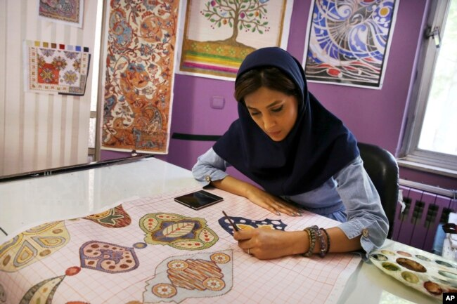 An Iranian woman sketches and paints carpet patterns at a workshop in the Cultural and Artistic
