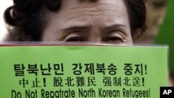 """一名""""脫北者""""高舉標語牌在中國駐南韓首爾大使館門前示威﹐抗議中國遣返""""脫北者""""。(資料圖片)"""