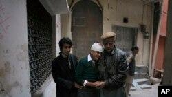 សាច់ញ្ញាតិកំពុងរំលែកទុក្ខសិស្ស Mohammad Baqair ដែលរងរបួស (កណ្តាល) ហើយម្តាយដែលជាគ្រូបង្រៀនក៏ត្រូវបានសម្លាប់ដោយក្រុមតាលីបាននៅ Peshawar នៃប្រទេសប៉ាគីស្ថាន កាលពីថ្ងៃទី១៦ ខែធ្នូ ឆ្នាំ២០១៤។