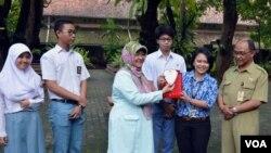 Pauline Arifin dari KPK menyerahkan plakat kepada Dwi Rini Wulandari Kepala Sekolah SMAN 3 Yogyakarta atas sikap jujur yang ditunjukkan para siswanya. (Foto: VOA/Munarsih Sahana)