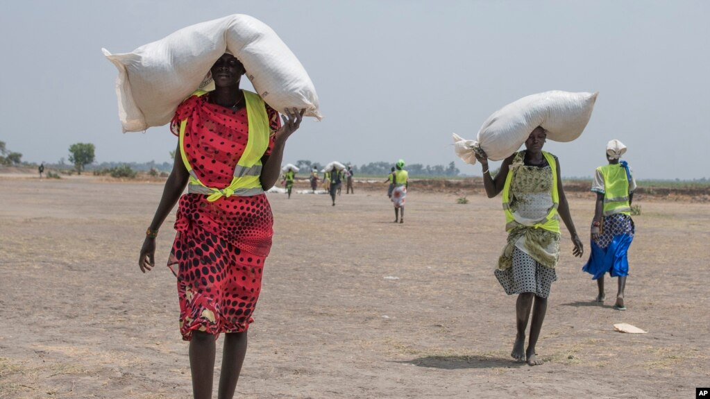 A women walk back to their homes after receiving food distributed by ICRC at a site in Leer County region of South Sudan, Tuesday, April 11, 2017. Two months after a famine was declared in two counties amid its civil war, hunger has become more widespread than expected, aid workers say, region on the brink of starvation and people at risk of dying without sustained food assistance.