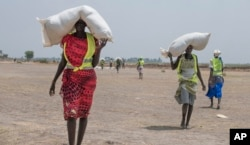 FILE - Women walk back to their homes after receiving food distributed by the International Committee of the Red Cross at a site in the Leer County region of South Sudan, April 11, 2017. Two months after a famine was declared in two counties amid civil war, hunger has become more widespread than expected, aid workers say.