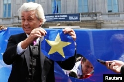 FILE - Dutch far-right Freedom Party leader Geert Wilders holds a star he cut from a European Union flag during a Eurosceptic rally in front of the EU Parliament in Brussels, Belgium, May 20, 2014.