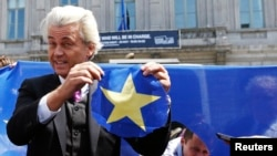 Dutch far-right Freedom Party leader Geert Wilders holds a star he cut from a European Union flag during a Eurosceptic rally in front of the EU Parliament in Brussels, Belgium, May 20, 2014.