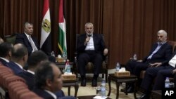 Head of the Hamas political bureau, Ismail Haniyeh, center, and Hamas leader in the Gaza Strip Yahya Sinwar, right, meet with Egypt's general intelligence chief, Khaled Fawzy, and others in Haniyeh's office in Gaza City, ahead of talks in Cairo, Oct. 3, 2017.
