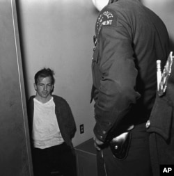 FILE - Lee Harvey Oswald sits in police custody shortly after being arrested in connection with the fatal shooting of President John F. Kennedy in Dallas, Texas, Nov. 22, 1963.