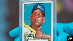 """The """"Holy Grail"""" of baseball cards, a 1952 Topps Mickey Mantle that is valued at more than $10 million, is put on display as part of baseball memorabilia exhibit at the Colorado History Museum Monday, July 16, 2018, in Denver. (AP Photo/David Zalubowski)"""