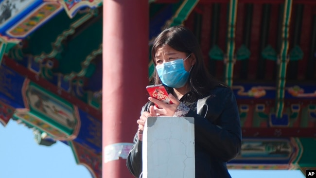 A woman wearing a face mask stands at a pagoda in Ritan Park in Beijing, Tuesday, Feb. 18, 2020. (AP Photo/Sam McNeil)
