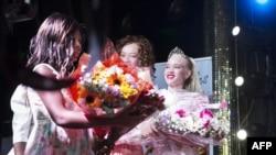 Sithembiso Mutukura, à droite, couronnée Miss albinos-Zimbabwe, reçoit un bouquet de fleurs lors du concours inaugural de beauté de ce genre, à Harare, le 17 mars 2018.