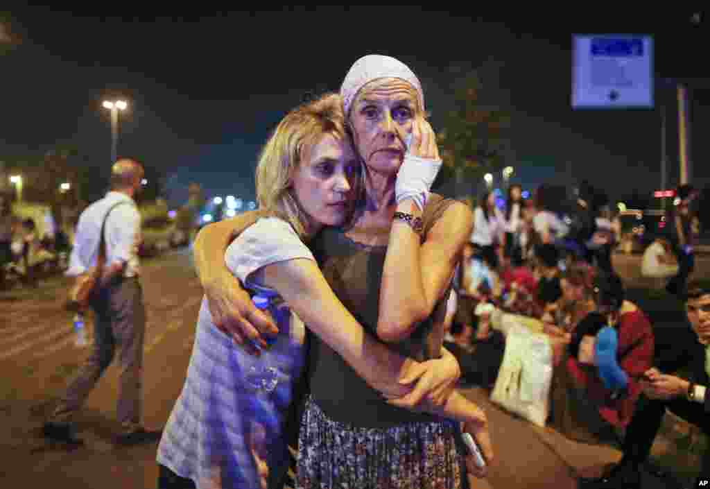 Passengers embrace each other early in the morning as they wait outside Istanbul's Ataturk airport in Turkey, following their evacuation in the wake of a number of explosions. The suicide bombing of the uspected Islamic State group extremists at the international terminal of the airport killed 41 people and wounded more than 200, said Turkish officials.