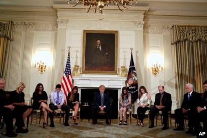 Presiden Donald Trump menundukkan kepalanya selama doa pembukaan pada awal sesi mendengarkan dengan siswa sekolah menengah dan guru di Ruang Makan Negara Gedung Putih di Washington, Rabu, 21 Februari 2018. (Foto: AP/Carolyn Kaster )