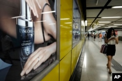 FILE - A woman walks past a Lacome advertisement at a subway station in Hong Kong, June 7, 2016.