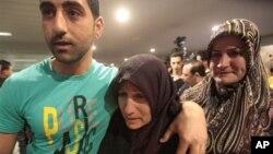 Salah seorang wanita Lebanon yang diculik di Suriah dan telah dibebaskan, dijemput kedua anaknya setibanya di bandara internasional Rafik Hariri, Beirut, Lebanon (23/5)/