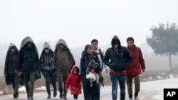 Sekelompok migran berjalan di perbatasan antara Serba dan Kroasia dekat desa Berkasovo, Serbia (19/10).