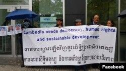 ពលរដ្ឋខ្មែរនៅអាល្លឺម៉ង់កាន់បដាទាមទារស្តារលិទ្ធិប្រជាធិបតេយ្យ ក្នុងពេលបាតុកម្មប្រឆាំងនឹងដំណើរទស្សនកិច្ចរបស់រដ្ឋមន្ត្រីកម្ពុជាចំនួនបួនរូបនៅទីក្រុងប៊ែរឡាំង ប្រទេសអាល្លឺម៉ង់ ថ្ងៃទី២៥ ខែកញ្ញា ឆ្នាំ២០១៩។ (Facebook/Netzwerk für Demokratie in Kambods)