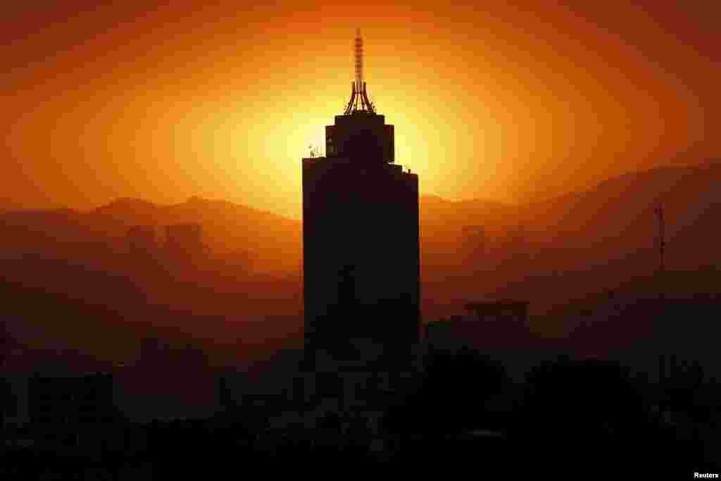 The sun sets behind the World Trade Center building in Mexico City, March 14, 2016.