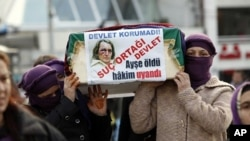 Women activists carry a mock coffin of Ayse Pasali, who was shot to death by her ex-husband, during a demonstration, planned as an alternative to Valentine's Day, in central Istanbul, February 14, 2011