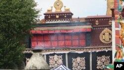 ພວກທະຫານຈີນເປ້ເຄື່ອງມອດໄຟຢູທາງຫລັງ ຍ່າງຢູ່ທາງໜ້າວັດ Jokhang ທີ່ນະຄອນ Lhasa, ບ່ອນທີ່ຊາຍສອງຄົນພະຍາຍາມ ໂຜໂຕເອງຕາຍ, ວັນທີ 28 ພຶດສະພາ 2012.