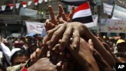 Waandamanaji wanaoipinga serikali ya Yemen wakishikana mikono wakati wa maandamano ya kumtaka Rais Ali Abdullah Saleh ajiuzulu huko Sana'a, May 24, 2011
