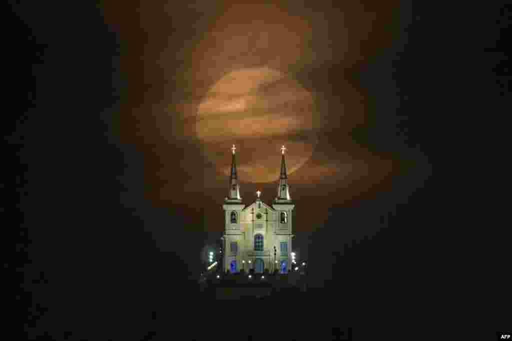 """当地时间8月10日,巴西里约热内卢一所寺庙后方的满月。这是一年中月球运行到轨道上最接近地球的时候,同时正好是满月。科学家称这种现象为""""超级月亮""""。"""