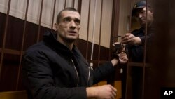 FILE - Russian artist Petr Pavlensky speaks to journalists as he sits in a cage in courtroom in Moscow, March 31, 2016. The artist, known for his political art performances, is one of three winners of the Human Rights Foundation's 2016 Vaclav Havel Prize for Creative Dissent.