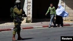 Palestinians walk near an Israeli soldier as he stands guard during an operation to locate three Israeli teens in the West Bank City of Hebron, June 17, 2014.