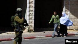 Palestinians walk near an Israeli sold