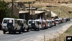 Photo released by the government-controlled Syrian Central Military Media shows ambulances of the Syrian Arab Red Crescent gathering in the Syrian border village of Fleeta, ahead of the evacuations of some Syrian refugees from Lebanon, July 31, 2017. T