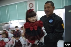 "A Thai policeman shows a ""luuk thep"" (child angel) doll after more than a hundred of them were seized in separate raids, at the Economic Crime Suppression Division in Bangkok, Jan. 26, 2016."